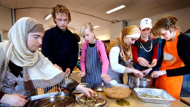 Leerlingen van de gereformeerde scholengemeenschap Guido de Bres in Amersfoort eten samen met hun ouders een islamitische maaltijd. Beeld Raymond Rutting