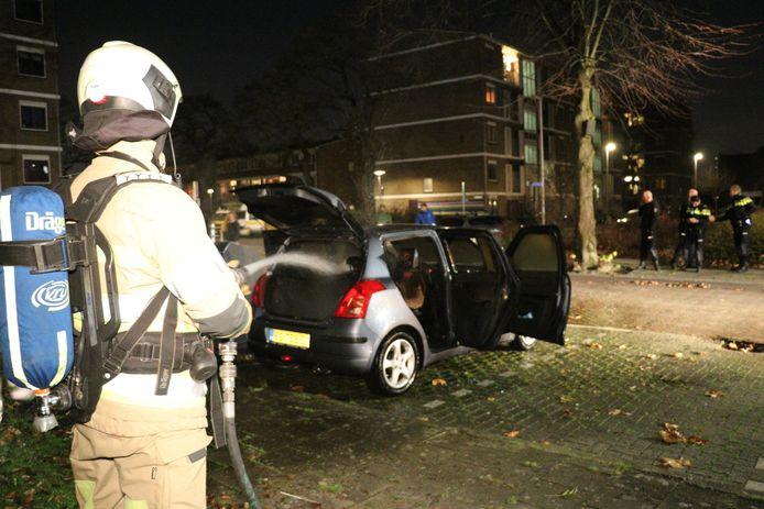 Een brandweerman blust de brandende auto aan de Houdringelaan in de Utrechtse wijk Hoograven.