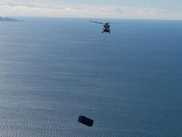 De legerheli vliegt de container over de Bay of Plenty.