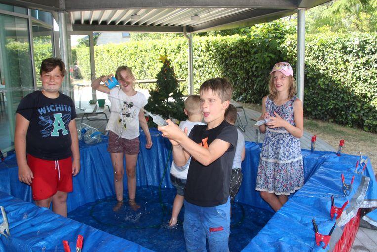 Enkele van de weinig aanwezige kinderen zoeken verkoeling in door de moni's zelfgebouwd zwembad.