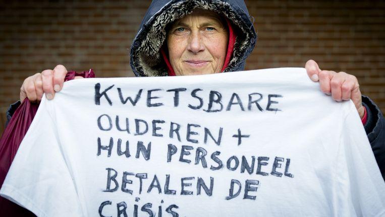 Een vrouw demonstreert in 2014 op het Binnenhof tegen de bezuinigingen op de langdurige zorg. Beeld anp