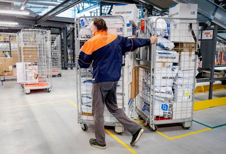 Medewerkers sorteren pakketten in het nieuwe pakketsorteercentrum van PostNL.  Beeld ANP
