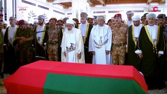 De nieuwe sultan Haitham bin Tariq al Said staat tussen de twee mannen in het wit bij de doodskist van de vorige sultan, Qaboos bin Said.