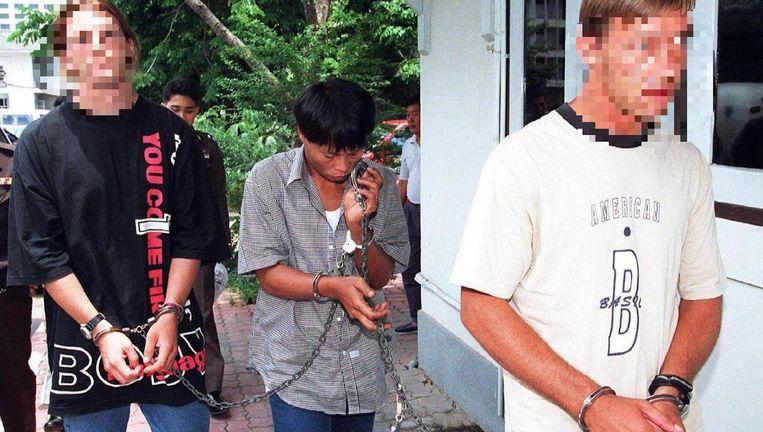Machiel Kuijt (r) wordt geboeid weggevoerd na zijn arrestatie in Bangkok wegens vermeende drugshandel op 17 april 1997. Beeld anp