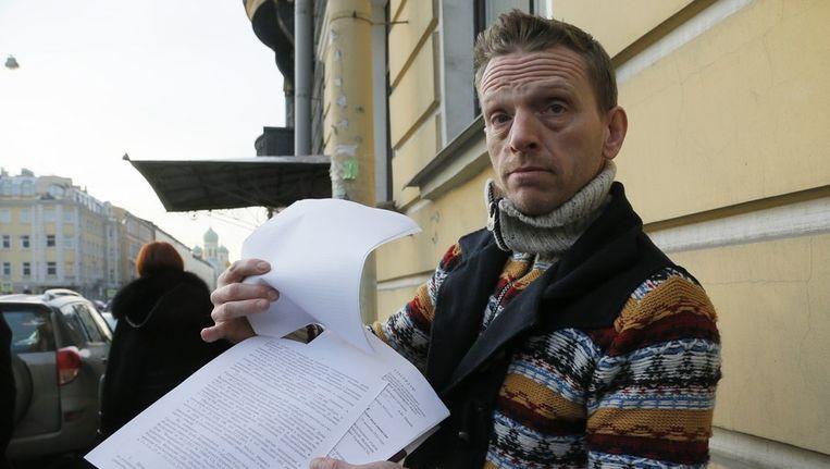 Greenpeace-acticist Mannes Ubels laat journalisten zijn papieren zien voor het immigratiekantoor in St. Petersburg Beeld ap