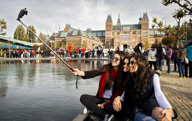 Braziliaanse toeristen maken een selfie op het Museumplein. Het aantal toeristen in Amsterdam is volgens berekeningen van het CBS de afgelopen jaren alleen maar gestegen. Beeld anp