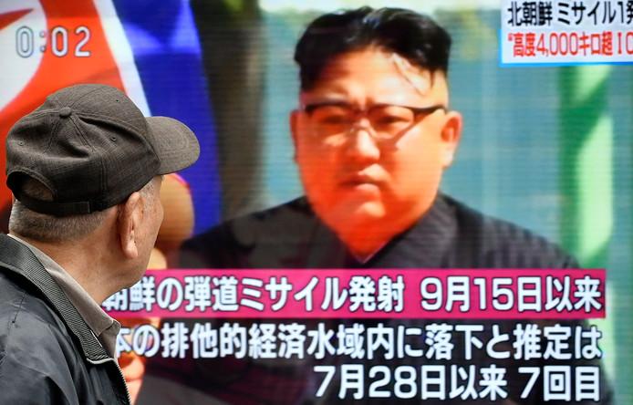 Een voetganger in de Japanse hoofdstad Tokio passeert een beeldscherm met een afbeelding van de Noord-Koreaanse leider Kim Jong-un.