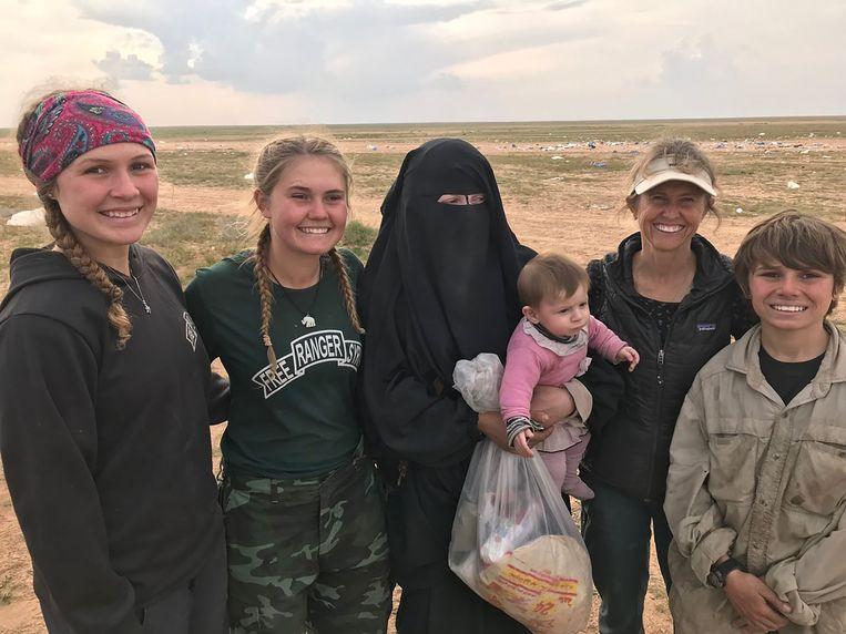 Sahale (17), Suuzanne (15), ma Karen (49) en Peter (12) bij de gesluierde vrouw die zopas haar zus is verloren. De tienerkinderen verplegen IS'ers in Baghouz, en delen water en brood uit. En na het water en brood ook Bijbels.