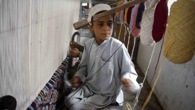 Een jongetje in Pakistan werkt in een weverij. Beeld ap