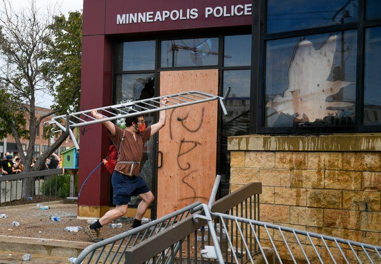 Een demonstrant bewerkt het politiebureau met een ijzeren dranghek. Beeld EPA