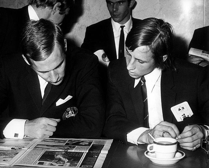 Jan van Beveren en Johan Cruijff lezen samen het laatse voetbalnieuws in 1969 voor het vertrek naar Polen op Schiphol. foto ANEFO