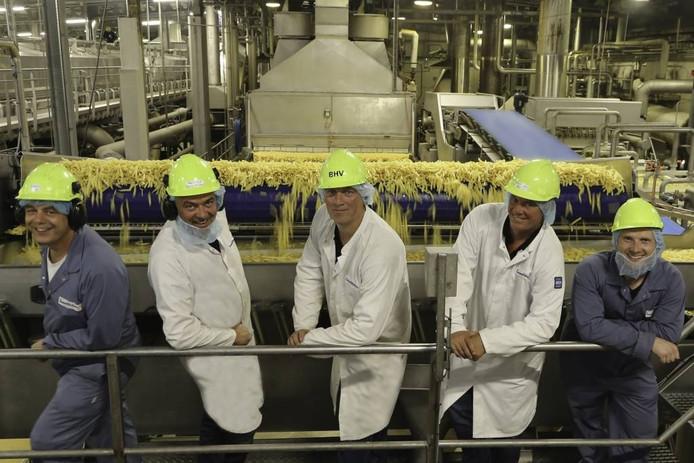 """Plantmanager Bert Jan Maris (tweede van rechts) is trots op het resultaat van de verbouwing van zijn bedrijf. """"We kregen hulp van over de hele wereld."""" Naast Maris enkele medewerkers, op de achtergrond de productielijn. foto Lamb Weston/Meijer"""