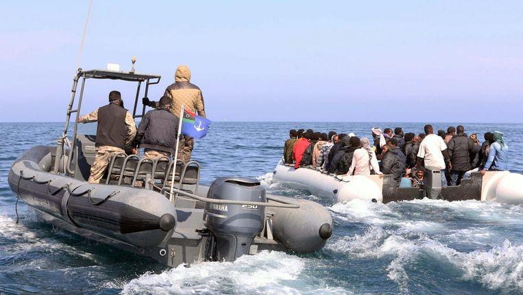 De Libische kustwacht sleept een boot met illegale migranten mee. Beeld afp