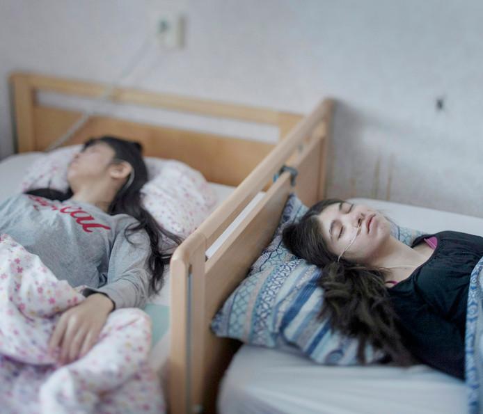 De foto door fotograaf Magnus Wennman toont twee zusjes die aan bed zijn gekluisterd door het 'uppgivenhetssyndrom', ook wel het 'terugtredingssyndroom'
