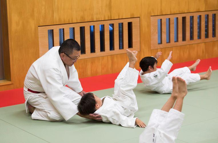 Judoleraar Tomoo Hamana beschermt tijdens een valtraining de nek van een jonge sporter.  Beeld AP