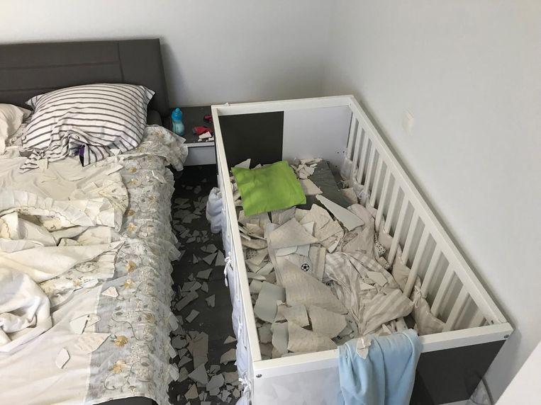 Het kinderbedje ligt vol brokstukken van het plafond.