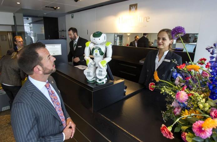 Foto: General manager Max Hermers (l) op de foto met hotelrobot Hugo en frontdeskmanager Kim Zeegers bij de balie van het Hampshire Crown Hotel Eindhoven.
