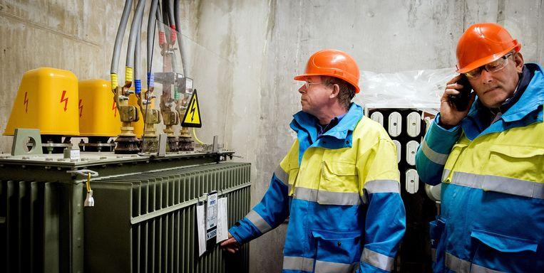 Medewerkers van Liander bij een transformator in Amsterdam.  Beeld ANP/Koen van Weel