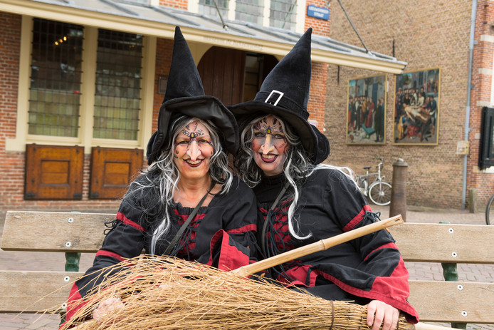 Heksen voor de Heksenwaag in Oudewater tijdens het evenement Heksenfestijn. Ingrid van der Wijngaard en Monique Bongers, beiden bestuurder van de Stichting Heksenfestijn, zijn als heks verkleed.