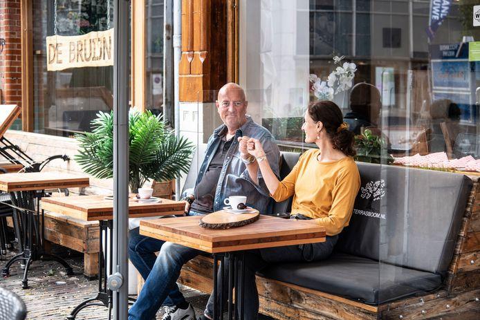 Mike en zijn vrouw Sharon Neuij op het terras van hun lunchzaak De Bruijn gescheiden door een plexiglas scherm vastgeschroefd op de houten bank.