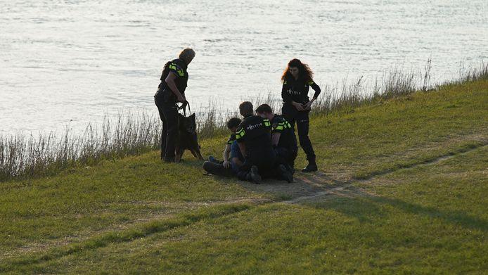 Politieagenten ovcermeesteren de man aan de stadskant van de IJssel in Deventer. Een wapen werd niet gevonden.