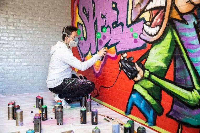 Wouter Loix spuit de laatste lik verf op de muurschildering in De Speeldoos, de buitenschoolse kinderopvang in Schulen bij Herk-de-Stad.