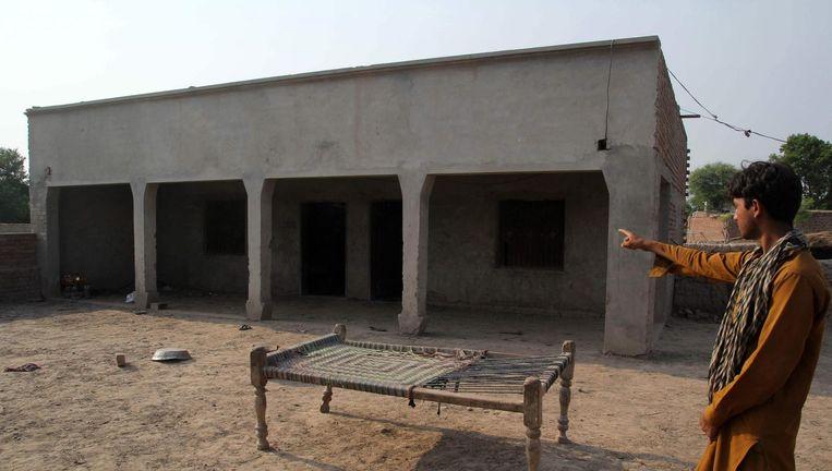 Een Pakistaanse inwoner wijst naar het huis waar een tienermeisje werd verkracht in Rajam Ram, Muzzaffarabad Beeld afp