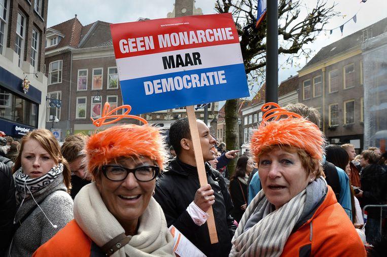 Een demonstrant tegen de monarchie tussen de feestvierders. Beeld Marcel van den Bergh / de Volkskrant