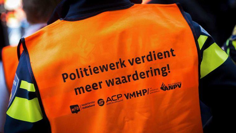 Een politieagent voert actie rond het Binnenhof. De actie houdt verband met de vastgelopen CAO-onderhandelingen met VVD-minister Ard van der Steur (Veiligheid en Justitie). Beeld anp