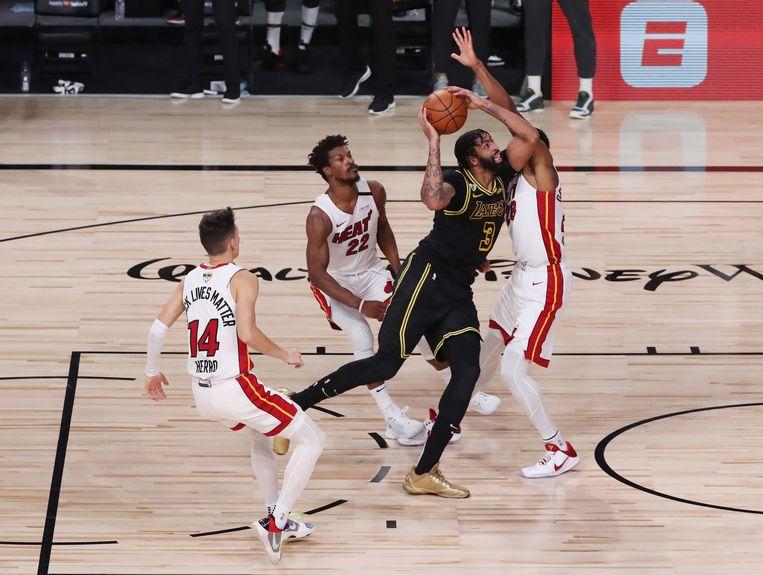 Anthony Davis van Los Angeles Lakers springt tussen verdedigers van Miami Heat door. Beeld AFP
