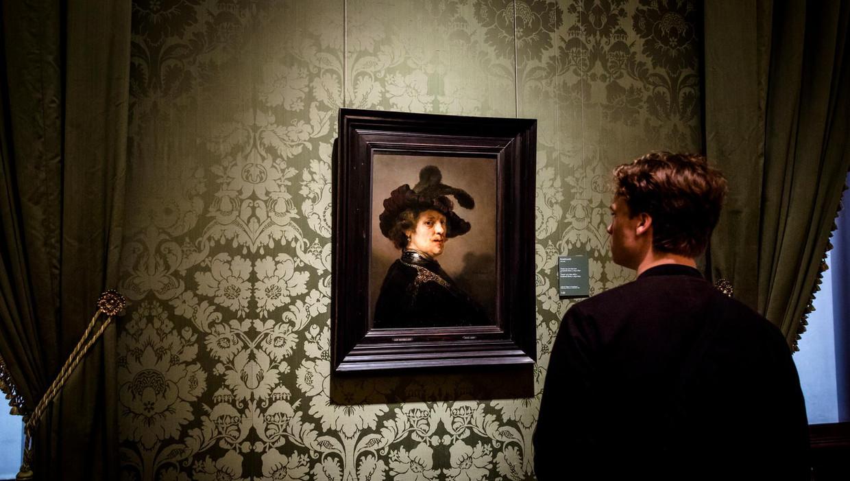 Een bezoeker kijkt in het Mauritshuis naar een schilderij van Rembrandt van Rijn.