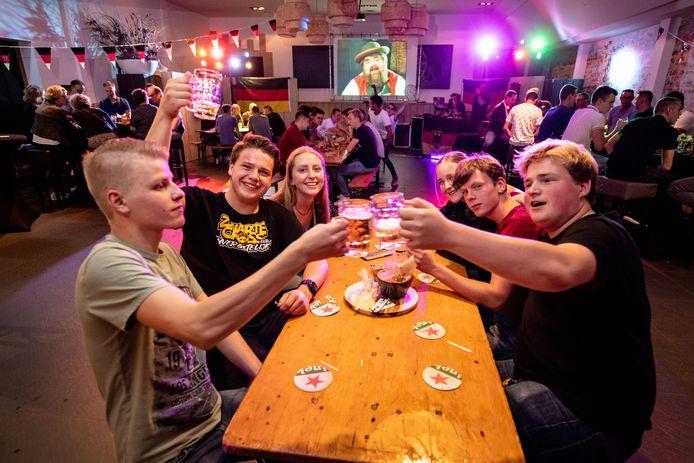 """Duitse feestavond bij café de Klok in Gendt. ,,Normaal loopt alles door elkaar heen, nu zit iedereen op afstand en op een vaste plek."""""""