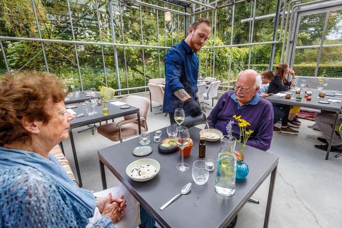 Gastheer Bouke Grob giet de aspergebouillon bij de asperges en zwarte sesamolie in De Tuinkamer in Schuinsloot.