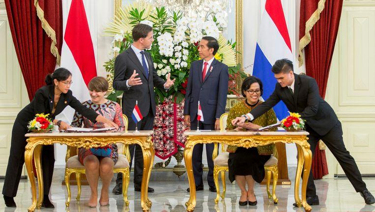 Premier Mark Rutte en de Indonesische president Joko Widodo staan achter Minister Lilianne Ploumen (l) van Buitenlandse Handel en Ontwikkelingssamenwerking en een lid van het Indonesische kabinet tijdens een ondertekening ceremonie op het Nationaal Paleis. Beeld anp