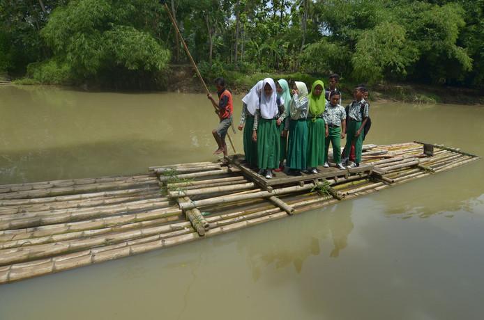 Indonesische Schoolkinderen uit Sukasari steken per bamboe vlot de Ciputrahaji Rivier  over op weg naar school. Foto Adeng Bustomi
