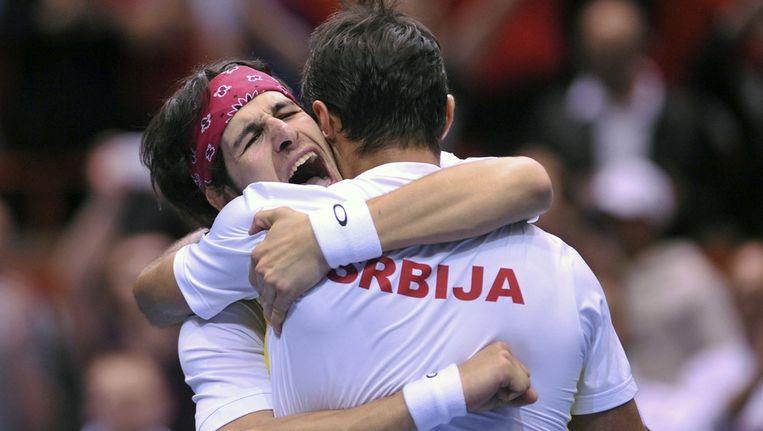 De Servische dubbelspelers Bozoljac (links) en Zimonjic vallen elkaar in de armen na hun thriller tegen Mike en Bob Bryan.