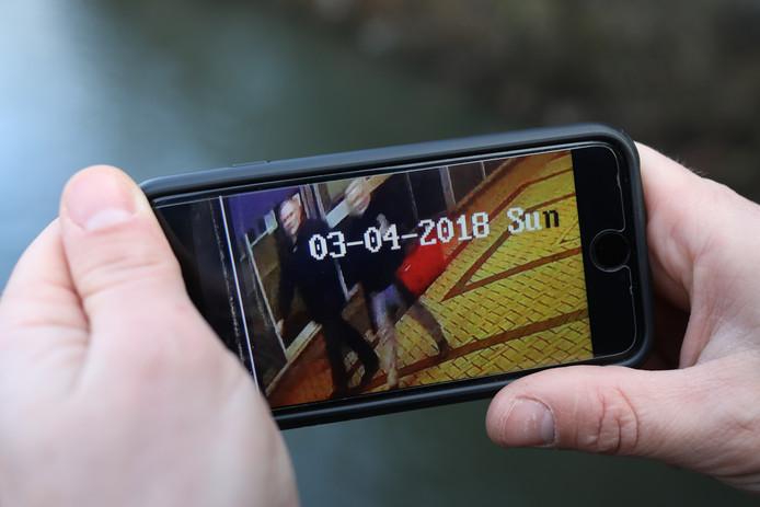 Een journalist laat de bewakingsbeelden zien die de politie bestudeert. Op de beelden zijn een man en vrouw te zien vlakbij de plek waar Skripal en de vrouw werden aangetroffen.