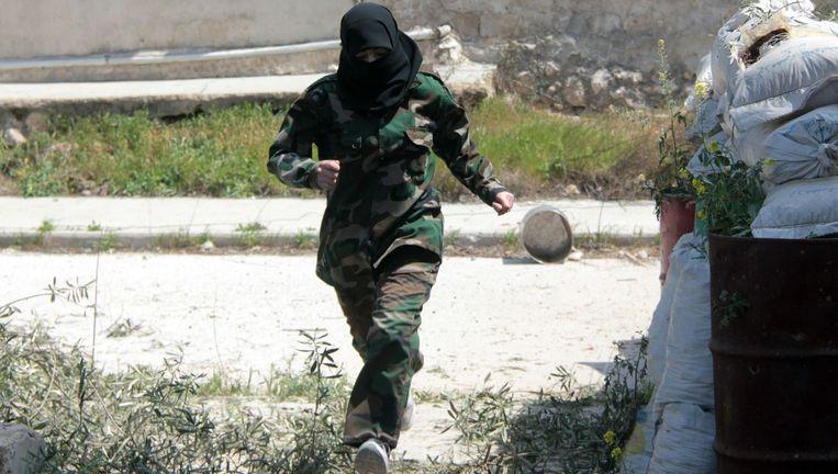 Een vrouwelijke strijder tijdens een confrontatie tussen de opstandelingen en het leger van Assad. Beeld afp