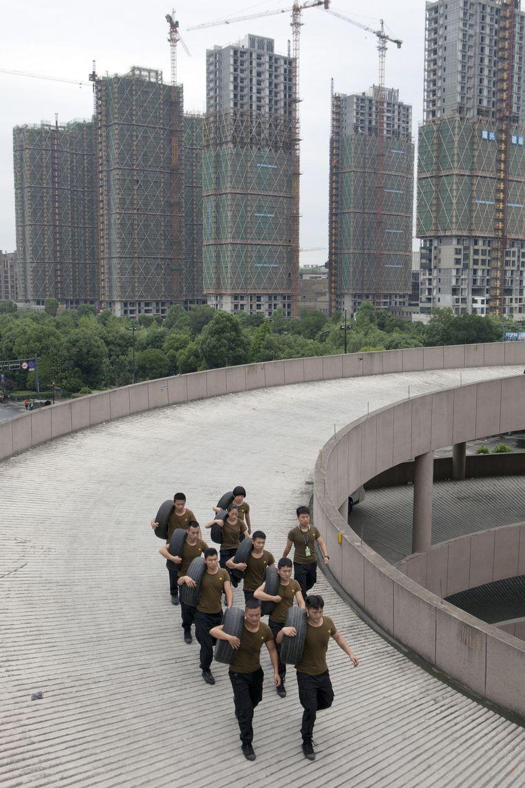 Training van bodyguards in wording op het dak van een parkeergarage in Hangzhou. Beeld Ruben Lundgren