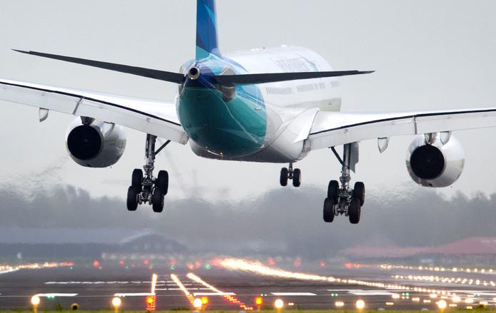 Een vliegtuig landt door de wind bijna haaks op de baan op Schiphol