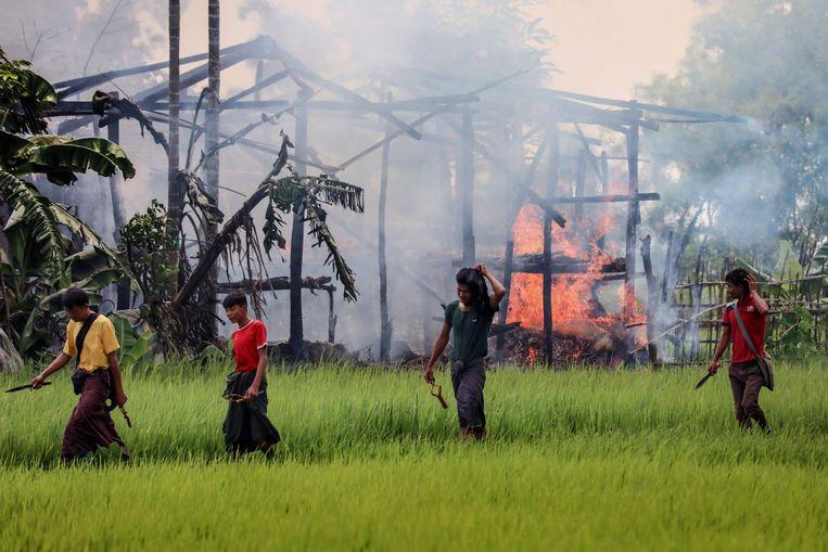 Gewapende mannen lopen in 2017 in een dorp in de provincie Rakhine langs in brand gestoken huizen van Rohingya's. Beeld AFP
