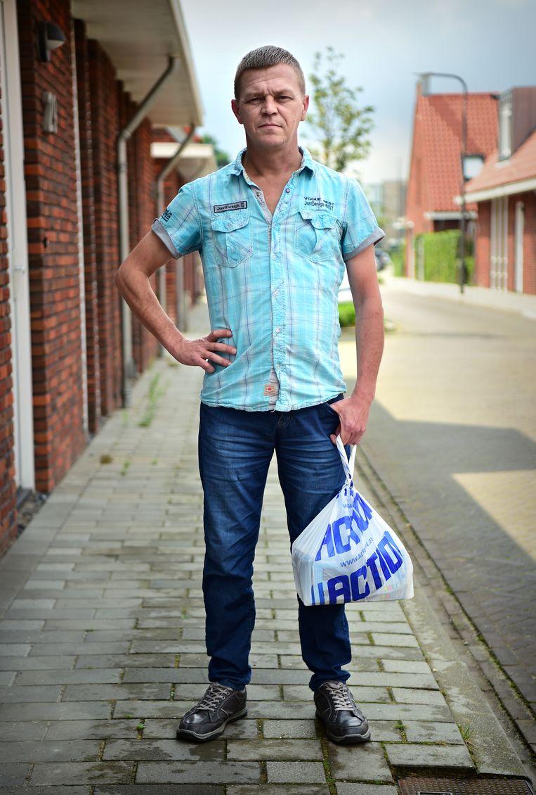 Action-medewerker Dennis Kossink met het tasje dat hem zijn baan kostte.  Beeld Marcel van den Bergh / de Volkskrant