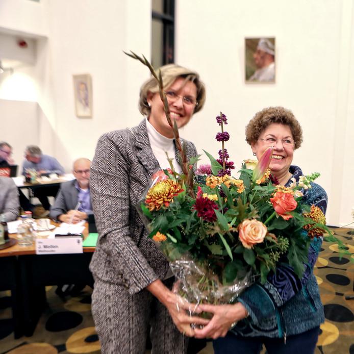 Toos Verschuur krijgt uit handen van de burgemeester een bos bloemen uitgereikt  in verband met haar afscheid van de Halderbergse raad. Foto Chris van Klinken