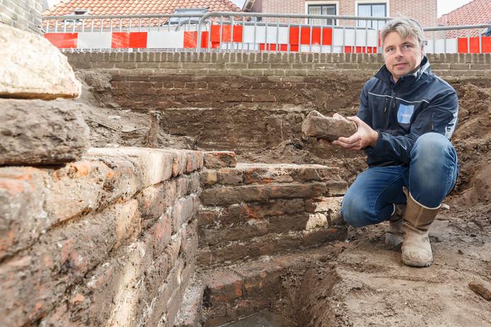 Archeoloog Michael Klomp bij de uit de dertiende eeuw daterende muren van de kerk, opgebouwd uit kloostermoppen.