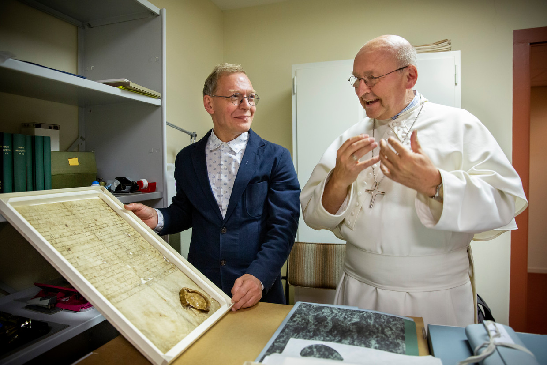 Archivaris Jan Sanders (links) en abt Denis Hendrickx bekijken de stichtingsakte uit 1134.