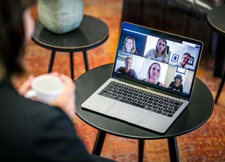 Een werknemer doet een videovergadering vanaf de bank bij haar thuis. Vanwege de coronacrisis werken steeds meer mensen vanuit huis, maar de werkplek thuis is niet altijd geschikt.  Beeld ANP, Remko de Waal