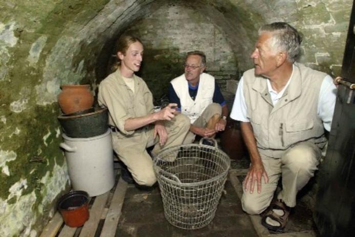 Molenaar Matthijs Bassie (l) geeft uitleg over de functie van de kelder die vroeger diende als aardappelopslagplaats. Foto AB HAKEBOOM