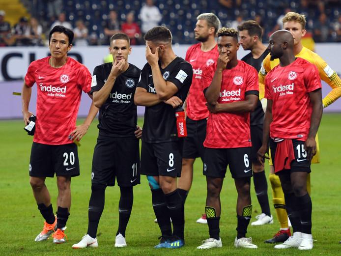 Jetro Willems,Jonathan de Guzmán en hun teamgenoten van Eintracht Frankfurt treuren na de flinke nederlaag.