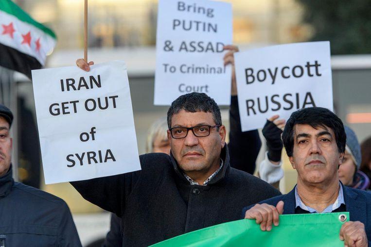 Tegenstanders van Russische en Iraanse inmenging in Syrië tijdens een demonstratie tegen het bombarderen van Aleppo op Place des Nations in Genève. Beeld null