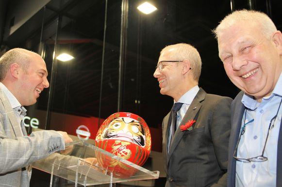 De grote baas van Nissan overhandigd een Daruma-pop aan Gilles Verhulst, vader Eddy kijkt tevreden toe